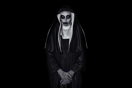 Portrait d'une religieuse maléfique effrayante, vêtue d'un habit noir et blanc typique, sur un fond noir, avec un espace vide autour d'elle