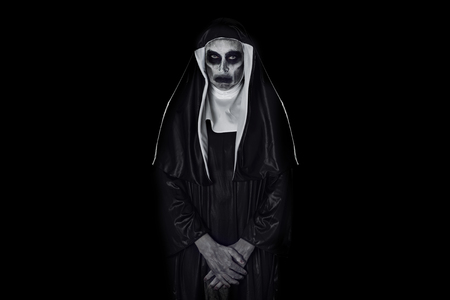 Retrato de una aterradora monja malvada, vestida con un hábito típico en blanco y negro, sobre un fondo negro, con un espacio en blanco a su alrededor