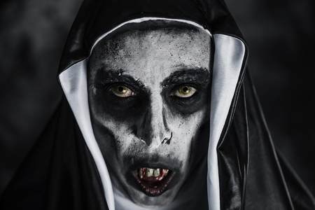 closeup of a frightening evil nun, with bloody teeth and scary eyes, wearing a typical black and white habit Archivio Fotografico