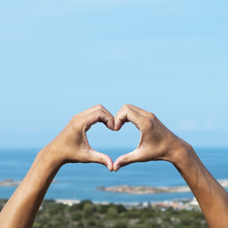 closeup of the hands of a young caucasian man forming a heart in front of the sea in the Southern coast of Corsica, in France