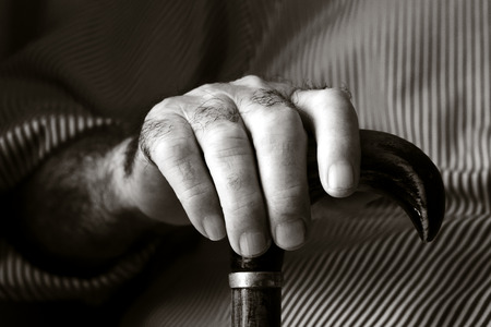 closeup of the hands of an old caucasian man with a walking stick, in a sepia toning