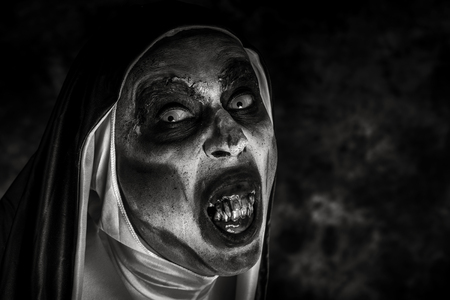 Closeup of a scary evil nun, with frightening teeth, wearing a typical black and white habit, in black and white Stock fotó