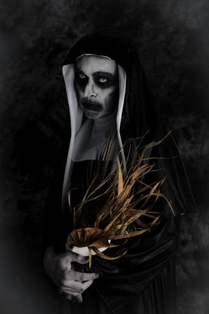 Portrait of a frightening evil nun, wearing a typical black and white habit, with a dry bouquet of flowers in her hands