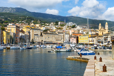 BASTIA, FRANCE - SEPTEMBER 16, 2018: A view of the Vieux Port, the Old Port of Bastia, in Corsica, France, higlighting the twin bell towers of the Saint-Jean-Baptiste church on the right