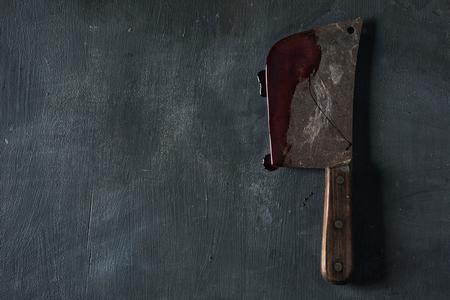 Vista de ángulo alto de un cuchillo de carnicero viejo y oxidado lleno de sangre, colocado sobre una superficie rústica de color verde oscuro, con un espacio en blanco a la izquierda Foto de archivo