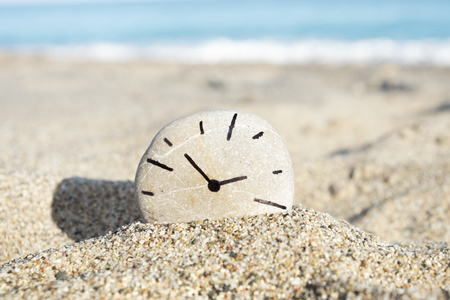 Closeup of a round stone with a clock Stock Photo