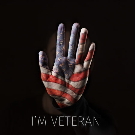 Closeup of the hand of man, with a flag of the United States patterned in his palm, emerging from the darkness and the text I am veteran