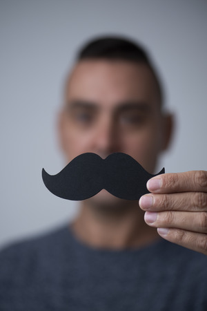 Closeup of a young caucasian man holding a fake mustache in front of his face