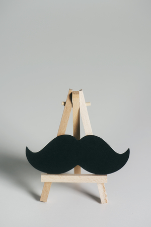 A black mustache on a wooden easel, on an on off-white