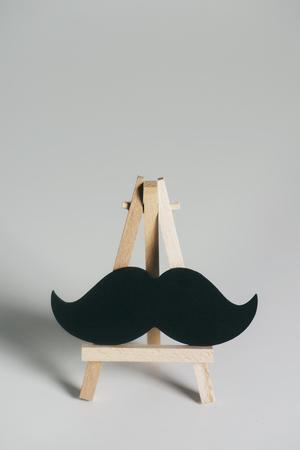Ein schwarzer Schnurrbart auf einer hölzernen Staffelei, auf einem auf gebrochenem Weiß Standard-Bild