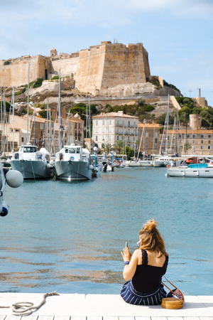 BONIFACIO, FRANCE - SEPTEMBER 19, 2018: A tourist takes pictures in the port of Bonifacio, in Corse, France, with the famous citadel of the city in the background, on the top of a promontory