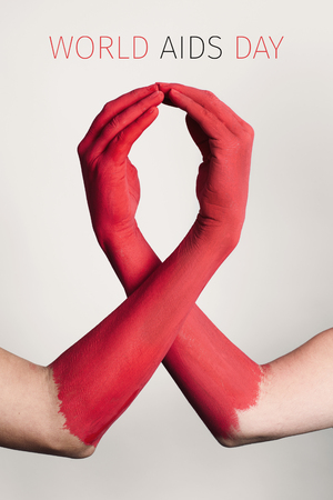 Closeup of the arms of two men painted red forming a red awareness ribbon and the text world aids day against an off-white