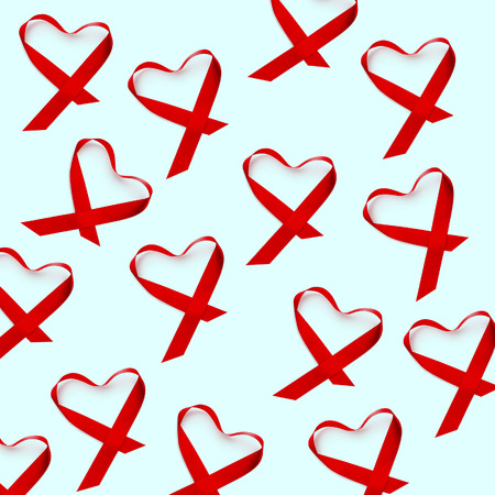 Some red ribbons, for the fight against AIDS, placed as hearts, on a pale green or pale blue
