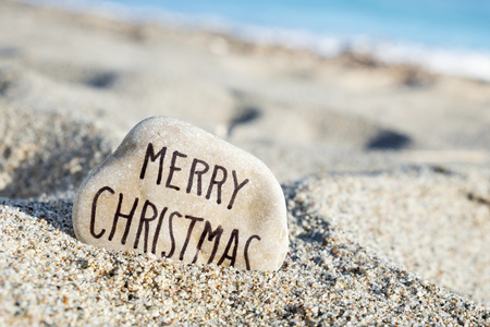 closeup of a stone, with the text merry christmas handwritten in it, on the sand of a lonely beach, with the ocean in the background