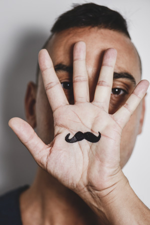 closeup of a young caucasian man with the palm of his hand in front of his face, with a mustache drawn in it Stock Photo