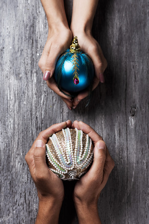 high angle view of a young caucasian woman and a young caucasian man with an ornamented christmas ball each one in their hands, on a gray rustic wooden table