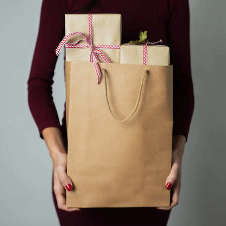 closeup of a young caucasian woman holding a paper shopping bag full of gifts against an off-white background Stockfoto