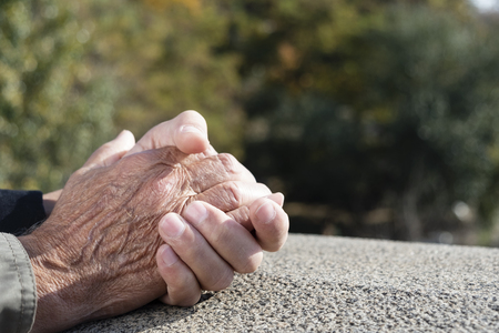 closeup of a young caucasian man holding the hand of an old caucasian man with affection outdoors