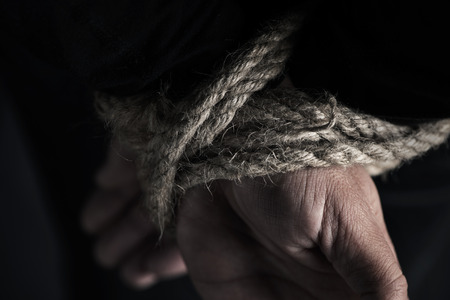 closeup of a man with his hands tied behind his back with rope, against a black background Stok Fotoğraf