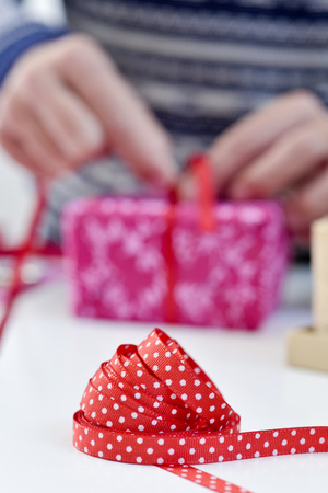 closeup of a young caucasian man tying a gift, wrapped in a nice pink paper, with a red ribbon, on a white table Stock Photo