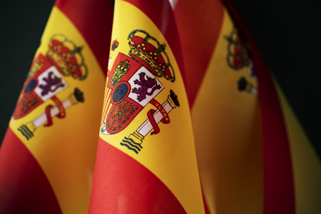 closeup of some flags of spain against a dark background 写真素材