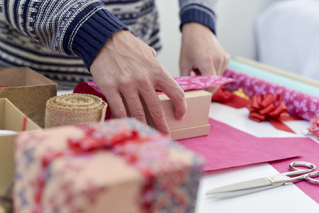 closeup of a young caucasian man wrapping a gift on a white table full of boxes, wrapping paper with different patterns and strings and ribbons of different colors