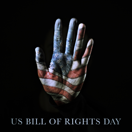 closeup of the palm of a hand patterned with the american flag and the text US bill of rights day written against a black background Stock Photo