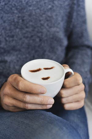closeup of a young caucasian man, sitting in a couch or an armchair, having a cup of cappuccino in his hands, with a happy face drawn with cocoa powder on its milk foam 스톡 콘텐츠