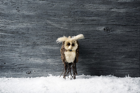closeup of a homemade owl-shaped ornament on the snow, against a gray rustic wooden surface with a blank space around it