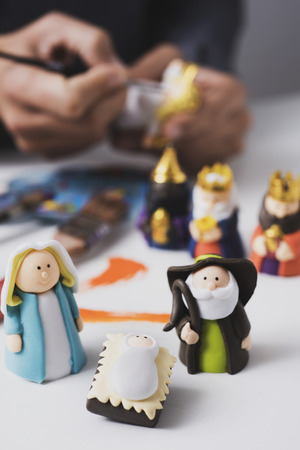 a caucasian man painting different handmade figurines of a nativity scene