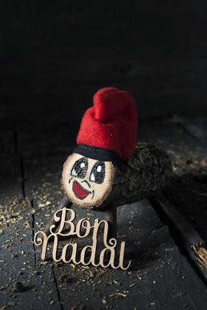 a handmade tio de nadal, a typical christmas character of catalonia, spain, and the text bon nadal, merry christmas written in catalan, on a gray rustic wooden surface, slightly lighted Banco de Imagens - 113821579
