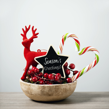 some different cozy christmas ornaments in a rustic earthenware tray and a black star-shaped signboard with the text seasons greetings written in it, on a rustic wooden surface, against a white wall