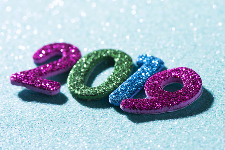 closeup of some glitter numbers of different colors forming the number 2019, as the new year, on a blue glitter background