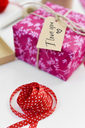 a nice gift, wrapped in a pink paper and tied with a string and a brown label attached to it with the text I love you written in it, on a white table next to a red ribbon patterned with white dots Stock Photo