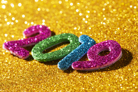 closeup of some glitter numbers of different colors forming the number 2019, as the new year, on a bright glittering yellow background