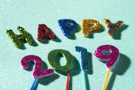 closeup of some glitter letters and numbers of different colors forming the text happy 2019, on a blue glitter background