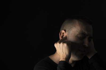 closeup of a suffering caucasian man with one hand in his head and the other hand covering his ear, on a black background, with some blank space on the left Reklamní fotografie