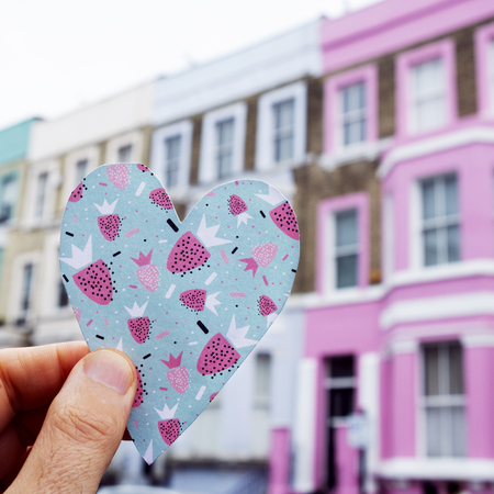 closeup of a caucasian man holding a heart cutout on a colorful paper, in front of a row of colorful houses in the popular portobello road in london, united kingdom