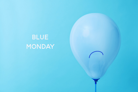 closeup of a blue balloon, with a sad face drawn in it, and the text blue monday on a blue background Stock Photo