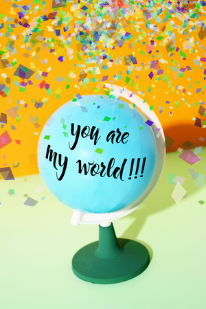 closeup of a blue terrestrial globe with the text you are my world written in it, on a green and orange background, while a pile of confetti is falling from above