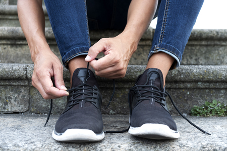 closeup of a young caucasian man, wearing denim pants, sitting on a staircase on the street, tying or untying the shoelaces of his sneakers