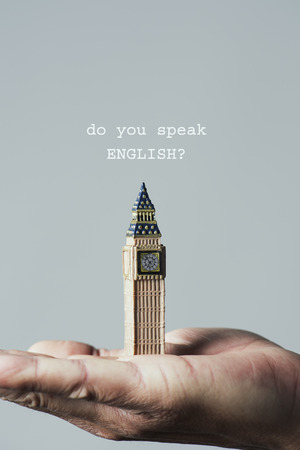 Closeup of the miniature of the Clock Tower of the Palace of Westminster in London, United Kingdom, on the hand of a caucasian man, and the question do you speak English on an off-white