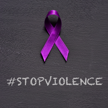 closeup of a purple ribbon, for the awareness about the unacceptability of the violence against women, and the text stop violence on a dark gray background 版權商用圖片 - 116325857