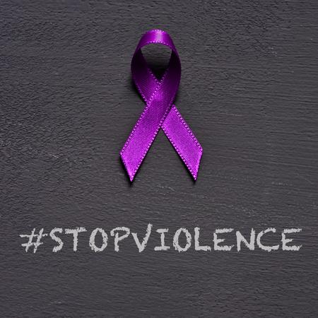 primo piano di un nastro viola, per la consapevolezza dell'inaccettabilità della violenza contro le donne, e il testo ferma la violenza su sfondo grigio scuro