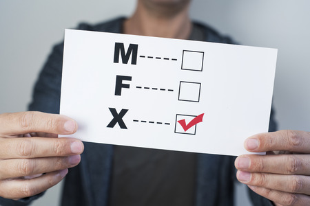 Closeup of a young caucasian person holding a form with the letters M for male, F for female and X for the third gender category, written in it, with a check mark on the X Banque d'images - 117263346