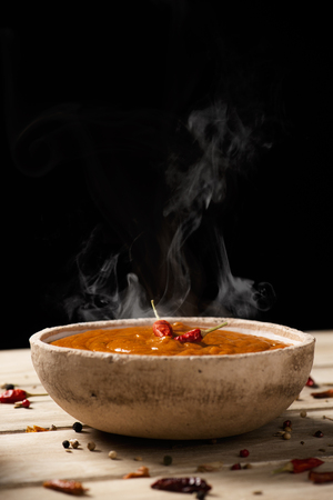 Closeup of an earthenware bowl with a chicken korma curry on a rustic wooden table, against a black