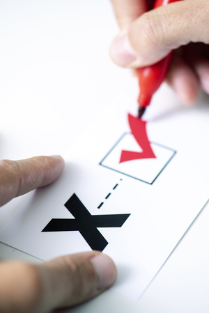 Closeup of a young caucasian person doing a check mark on a paper with a X written in it, for the third gender category