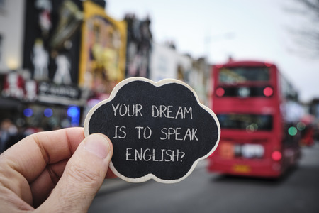 Closeup of the hand of a caucasian man holding a black signboard with the question your dream is to speak English written in it, on the street