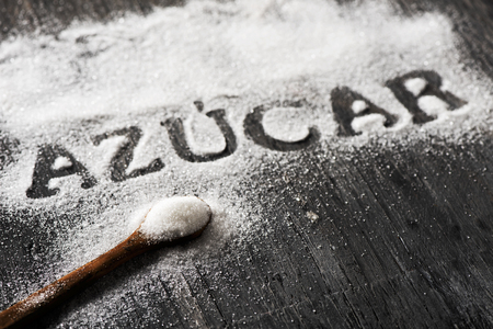 high angle view of a rustic gray wooden table sprinkled with sugar where you can read the word azucar, sugar written in Spanish, and a spoon full of sugar