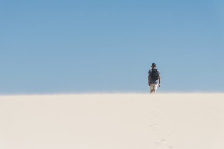 a young caucasian man, seen from behind, wearing a t-shirt and shorts, and carrying a backpack, walking by a white sand desert